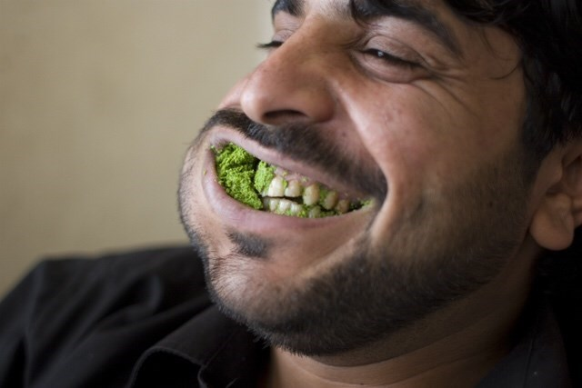 Gross pic of a guy chewing some green food with his mouth open