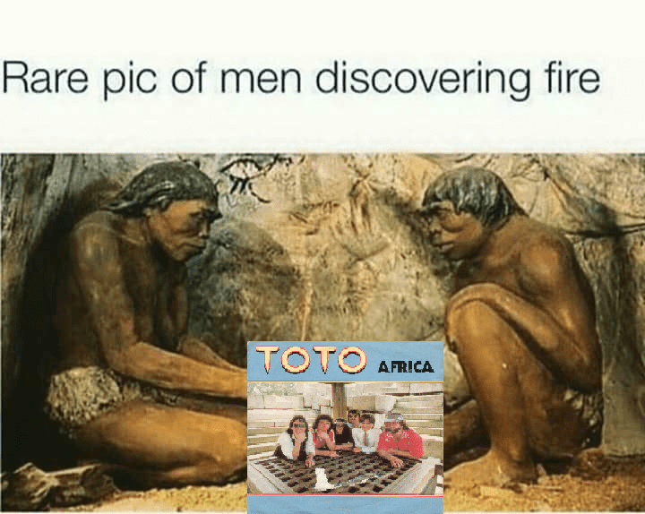 """Caption that reads, """"Rare pic of men discovering fire"""" above a pic of two cavemen with """"Toto"""" by Africa in between them"""