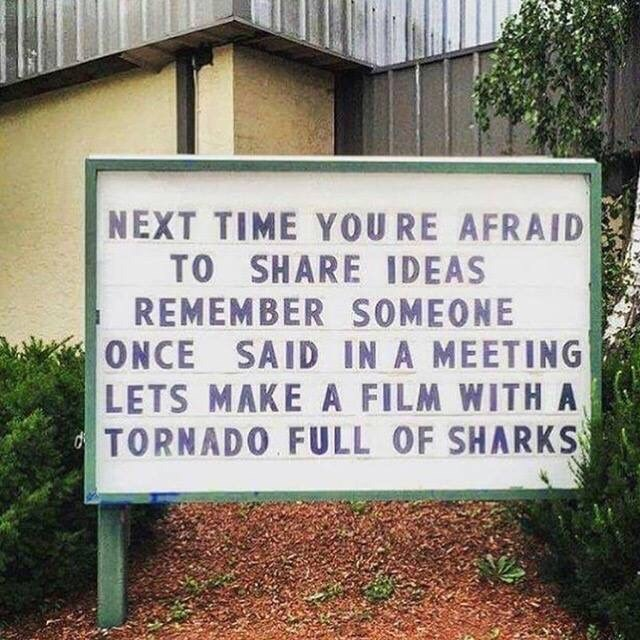 """Sign that reads, """"Next time you're afraid to share ideas remember someone once said in a meeting, 'Let's make a film with tornado full of sharks'"""""""