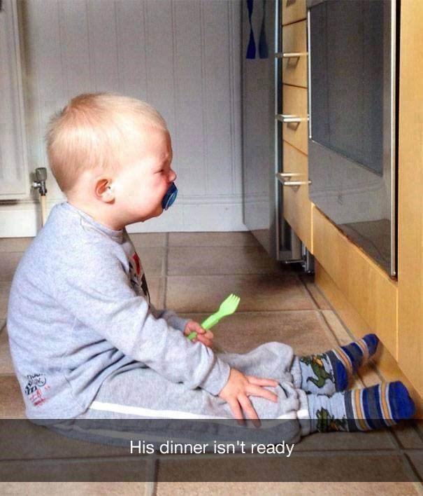 parenting meme of a baby crying while sitting in front of the oven because dinner isn't ready
