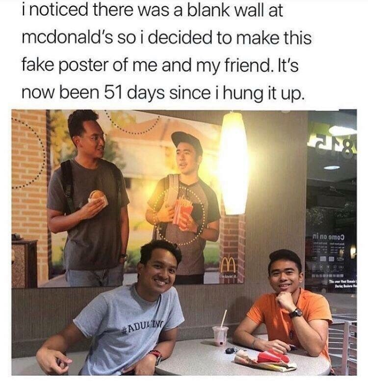 picture of smiling man under fake poster in McDonald's that he hung himself