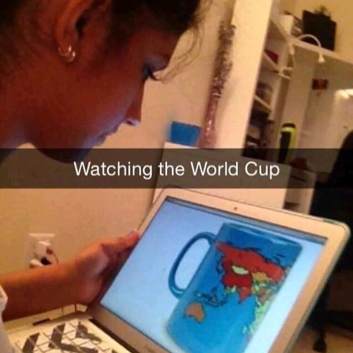 meme image of a girl looking at an image of a mug with a world map on it, and watching the world cup