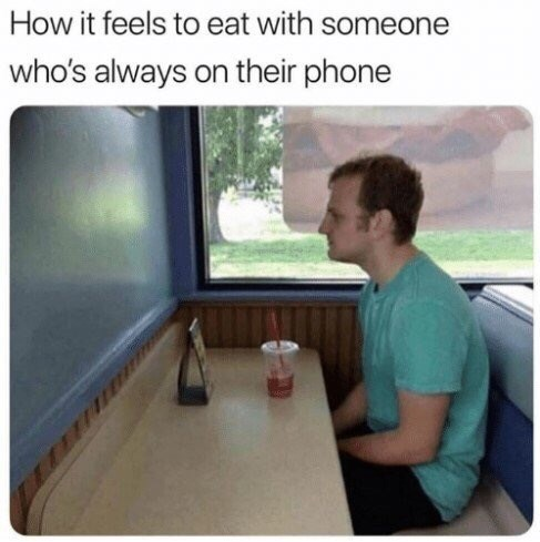 "Caption that reads, ""How it feels to eat with someone who's always on their phone"" above a pic of a guy at a restaurant sitting alone in a corner"