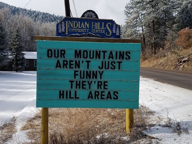 Street sign - INDIAN HILLS COMMUNITY CENTER OUR MOUNTAINS AREN'T JUST FUNNY THEY'RE HILL AREAS