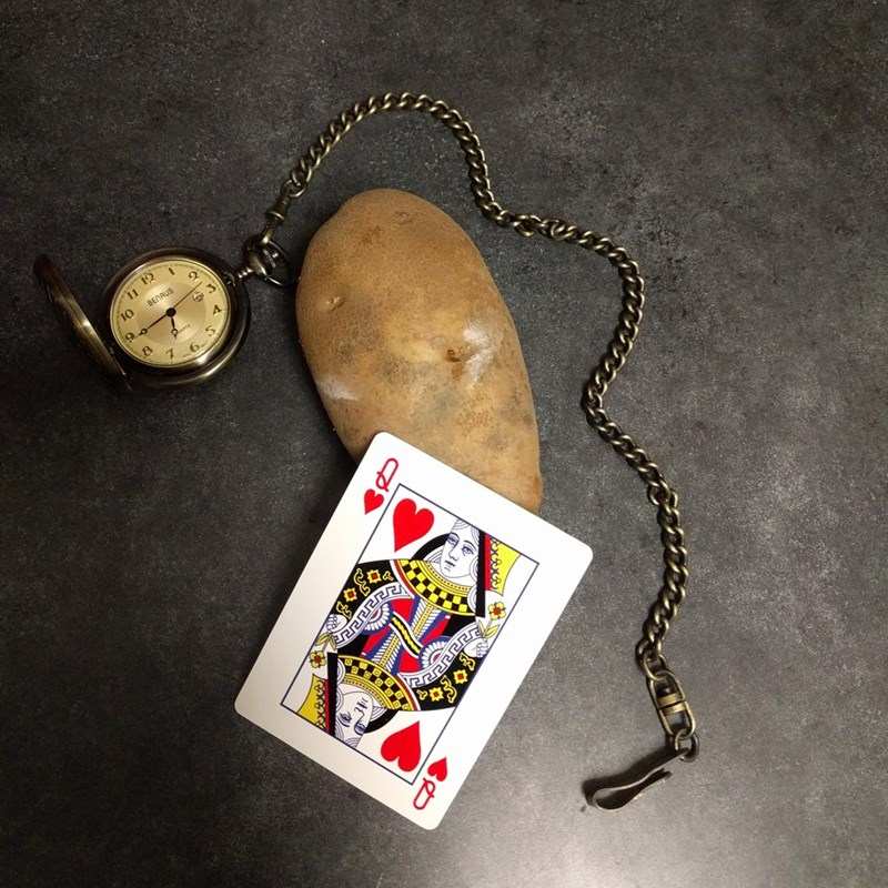 Disney's Alice represented by potato placed next to queen of hearts card and pocket watch