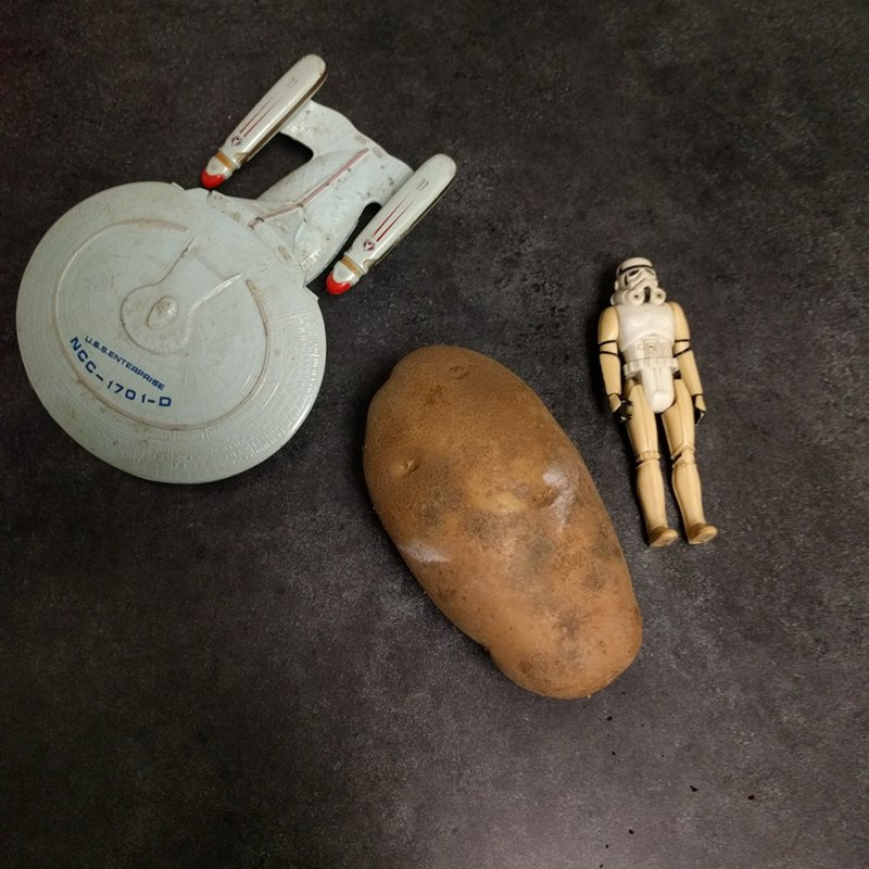 Princess Leia represented by potato next to Stormtrooper action figure and model of the Millennium Falcon