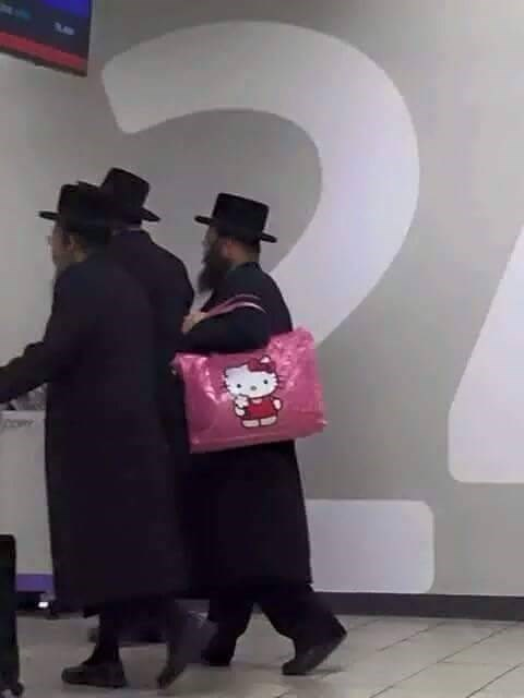 picture of Hassidic Jews in traditional clothes with one carrying a pink Hello Kitty bag