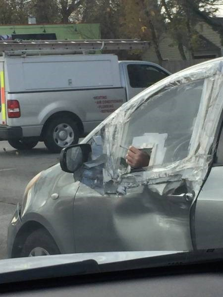 picture of taped up car window with small opening to smoke cigarettes through