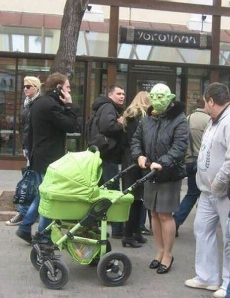 picture of woman pushing baby stroller in busy street and wearing green alien mask