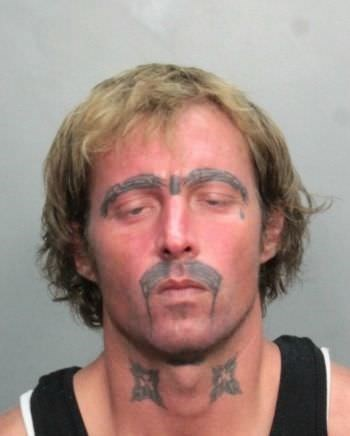 mug shot of man with tattooed eyebrows and mustache