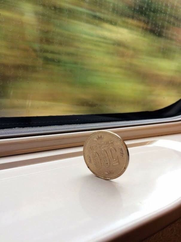 pic of coin balanced on its side in a moving train