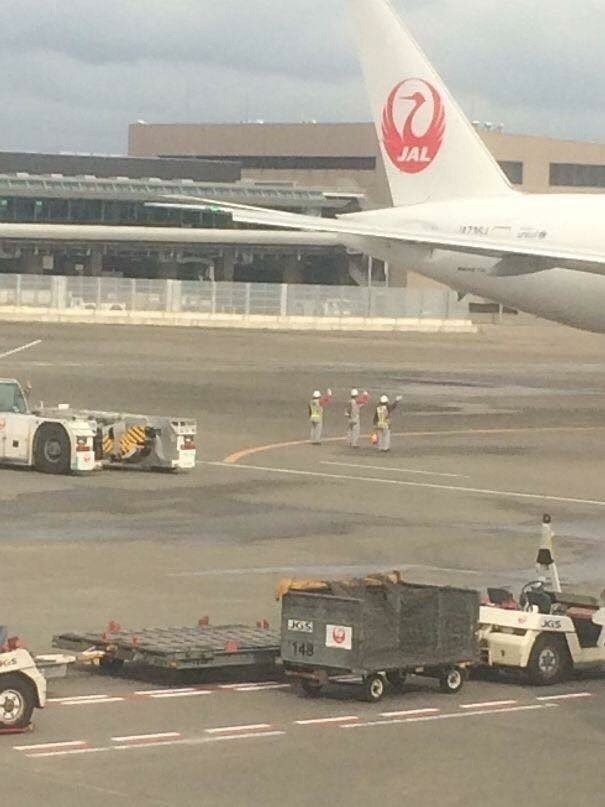 pic of Japanese airport loaders waving