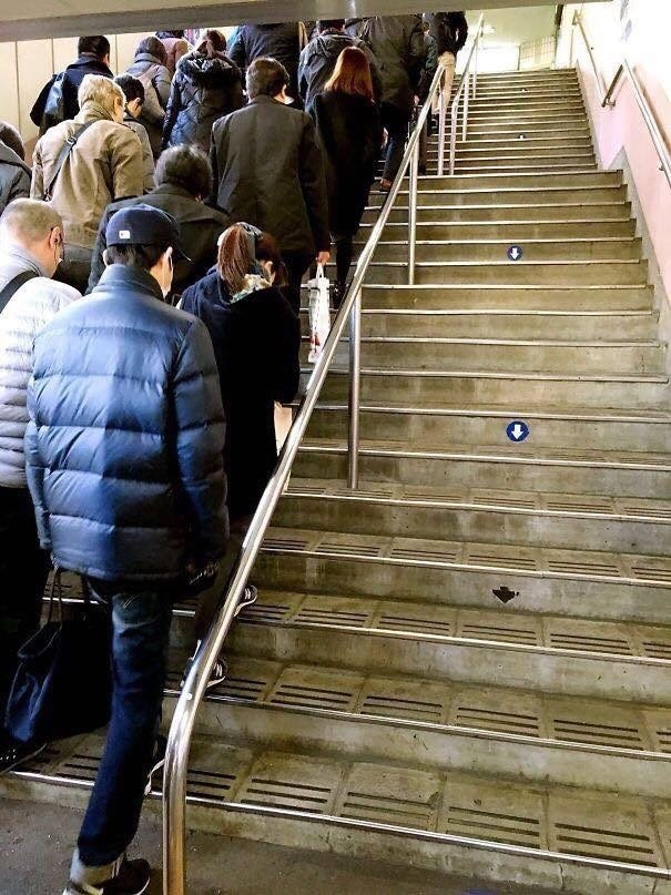 Pic of a bunch of people walking up some stairs and no one walking on the other side of the stairs