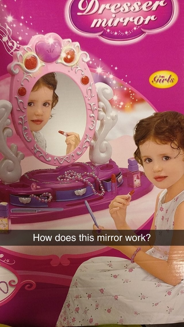image of a child's mirror set and the girl is looking away from the camera but her reflection is looking directly at her