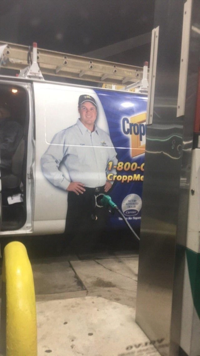 image of a gas station pump that is pumping a truck that has the image of a man directly in that spot