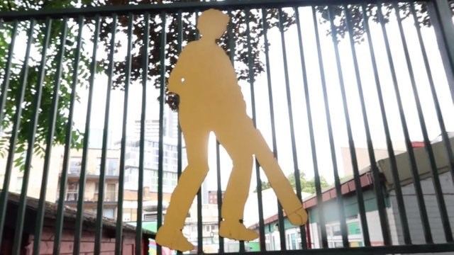 image of a gate and a figure of a man with his private parts out