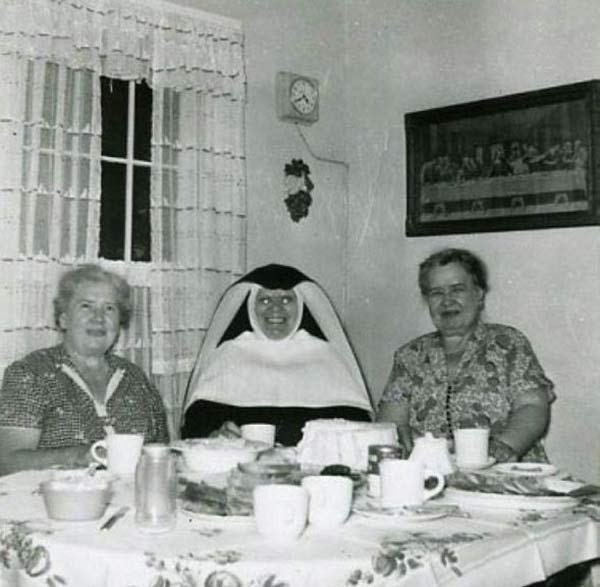 cursed image of demonic looking nun sitting between two old ladies at dinner table