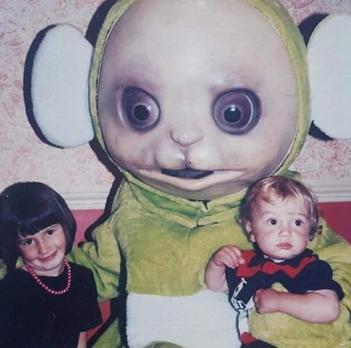 cursed image of demonic Teletubby with huge dark eyes photographed holding 2 small children