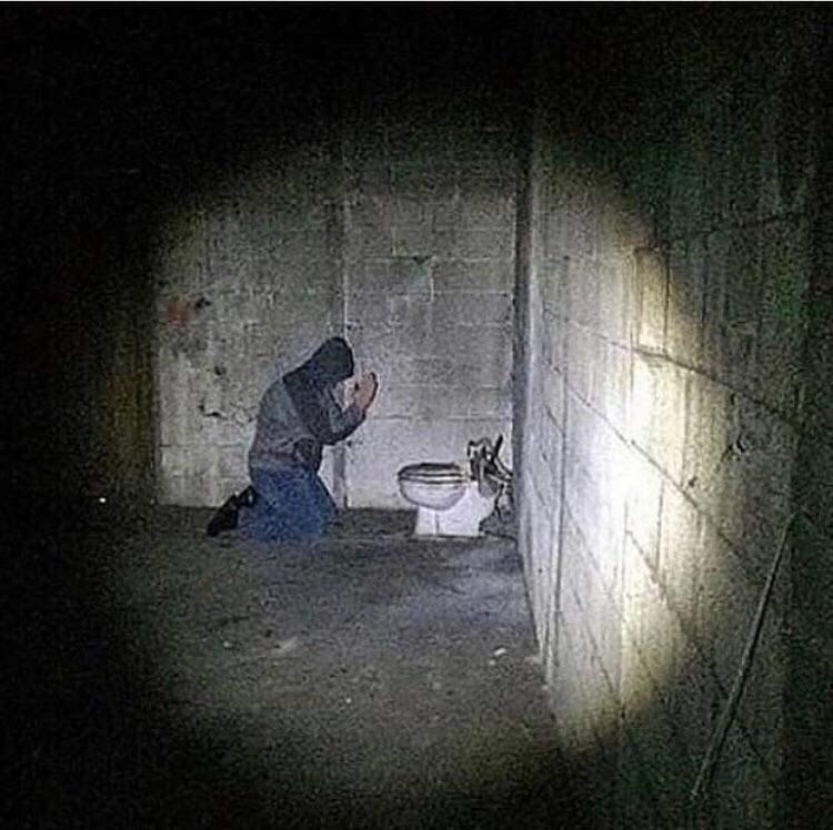 cursed image - man praying near a toilet
