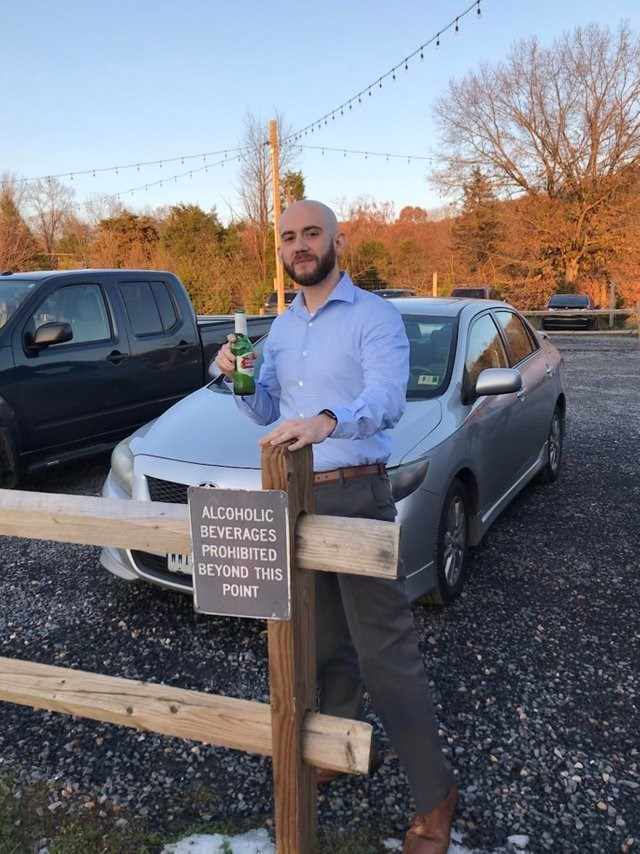 picture of rebellious man holding beer behind sign that forbids alcoholic beverages beyond it