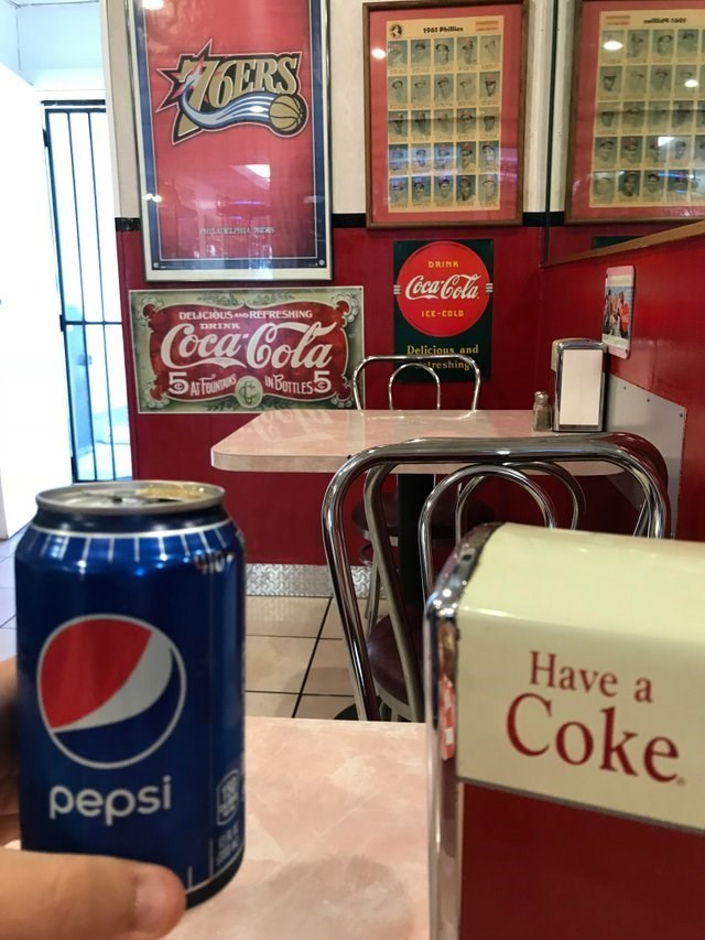 picture of person rebelliously having a Pepsi inside place filled with Coca Cola signs