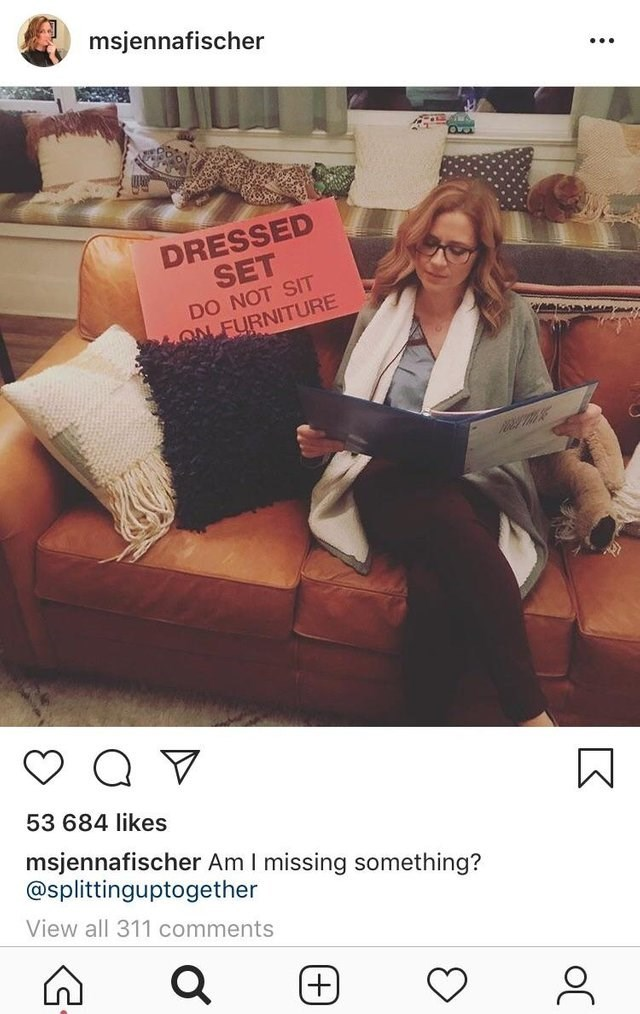 "picture of Jenna Fischer sitting on display sofa next to ""do not sit"" sign"