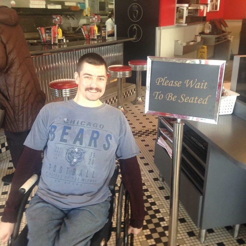 "picture of person in wheelchair posing next to ""please wait to be seated"" sign"