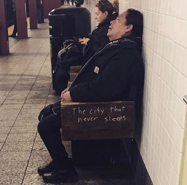 "picture of person napping on bench that reads ""city that never sleeps"""
