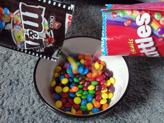 picture of Skittles and M&Ms being spilled into one bowl