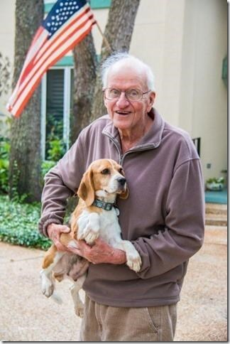 cute animal picture of grandpa holding newly adopted dog in his arms