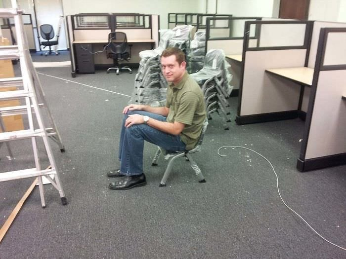 picture of fully grown man sitting on tiny kids chair