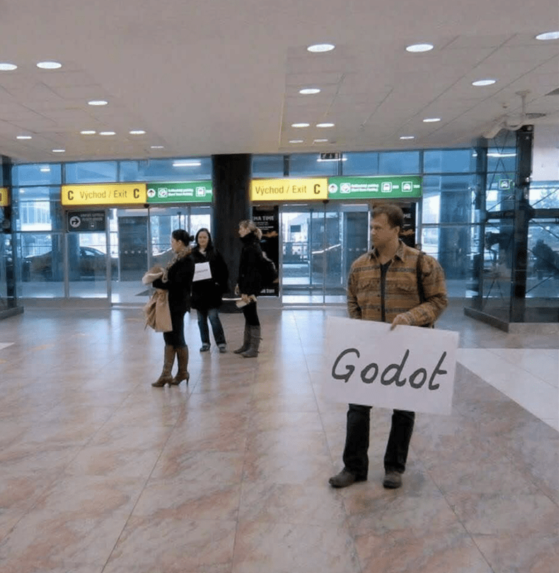 "Pic of a guy waiting for someone at an airport with a sign that says ""Godot"""