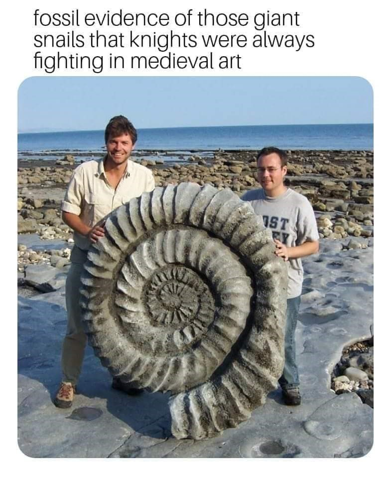 picture of two man holding up large spiral mollusc fossil that resembles monsters from medieval art