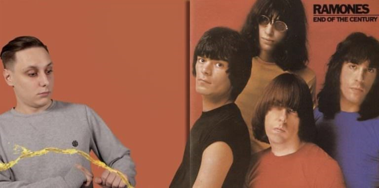 Guy stands next to The Ramones, where it looks like one of them is peeing on him