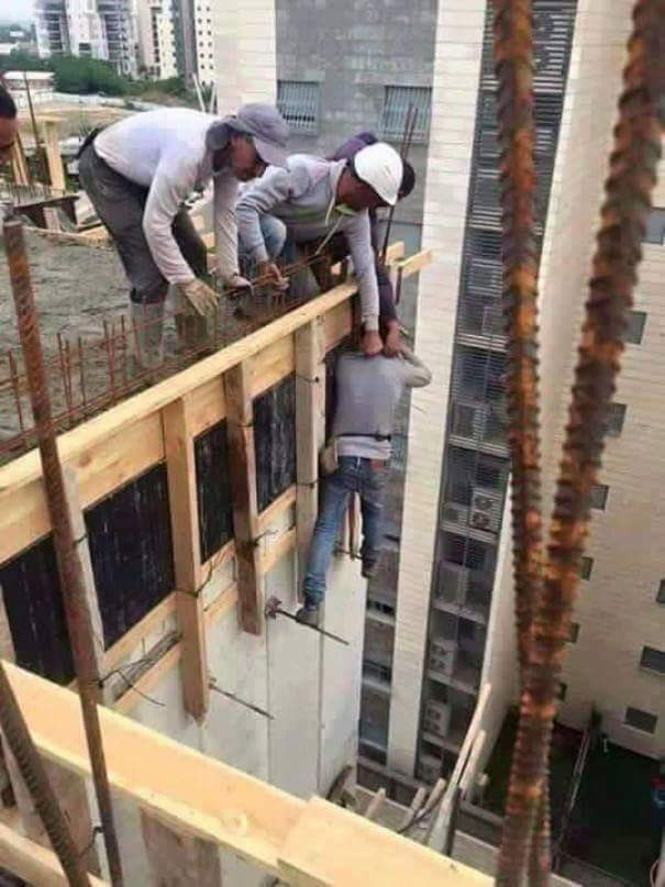 men tempting fate by holding onto a coworker off a building