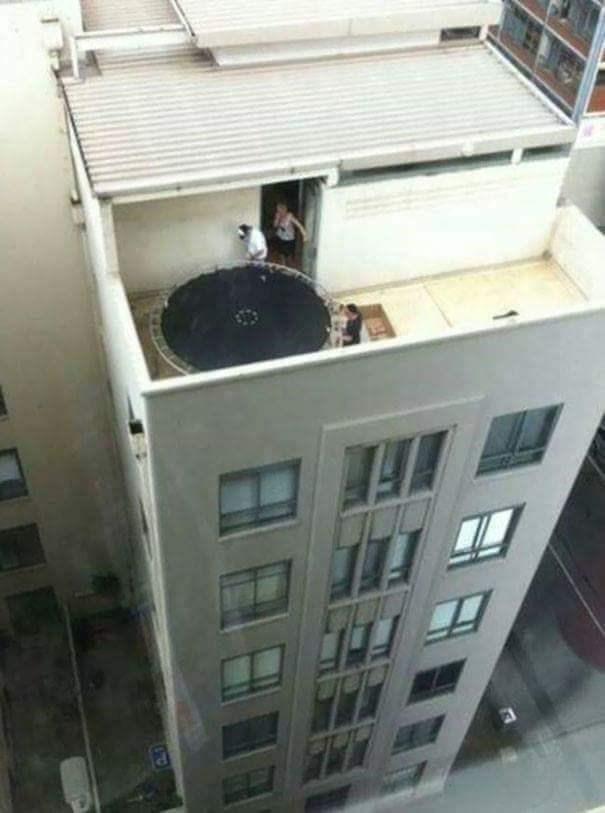 tempting fate by having a trampoline on a roof deck of a high rise building