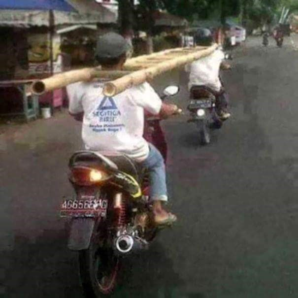 tempting fate by holding a ladder between two men on motorcycles