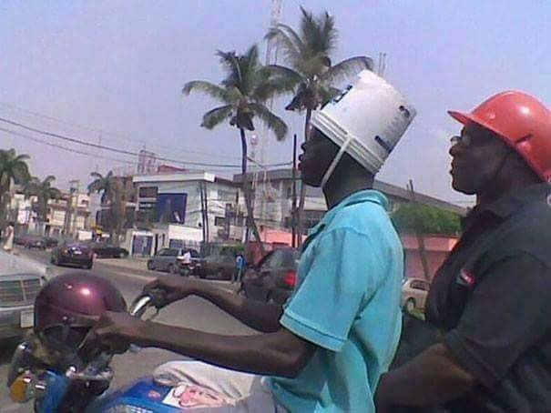 tempting fate by using a plastic bucket as a helmet on a motorcycle
