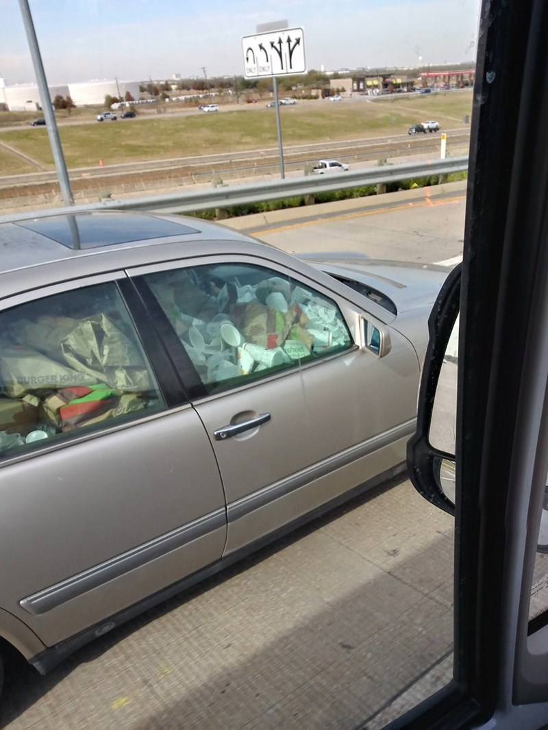 picture of car filled to the brim with trash and fast food wrappers