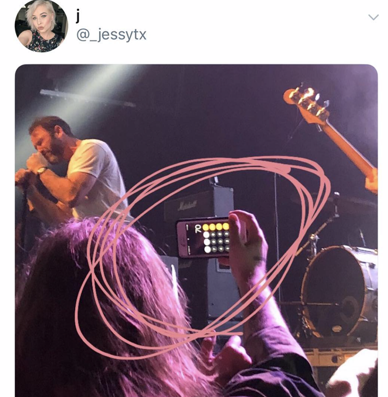 pic of a person at a concert holding up their phone to take a pic and the calculator is on