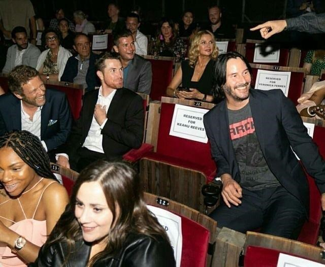 photo of Keanu Reeves sitting on chair next to one reserved for him