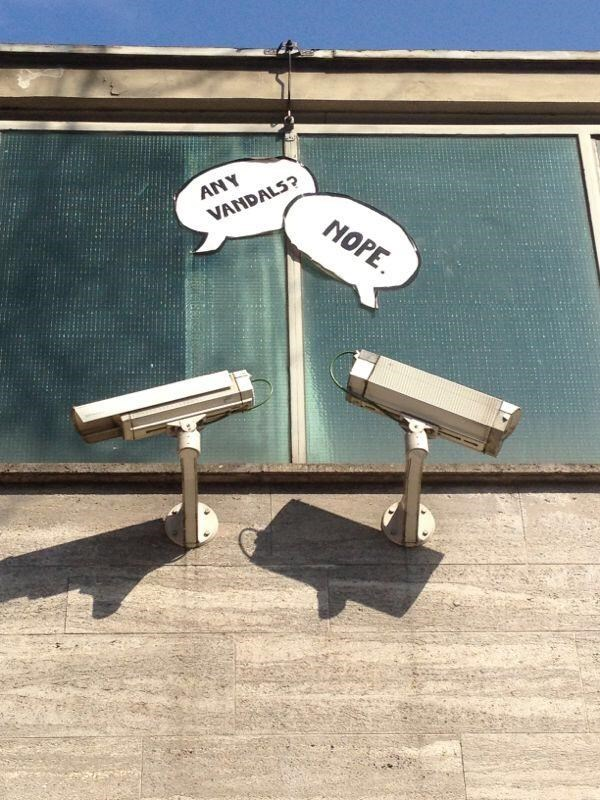 speech bubbles hung above two security cameras as if they're talking between each other