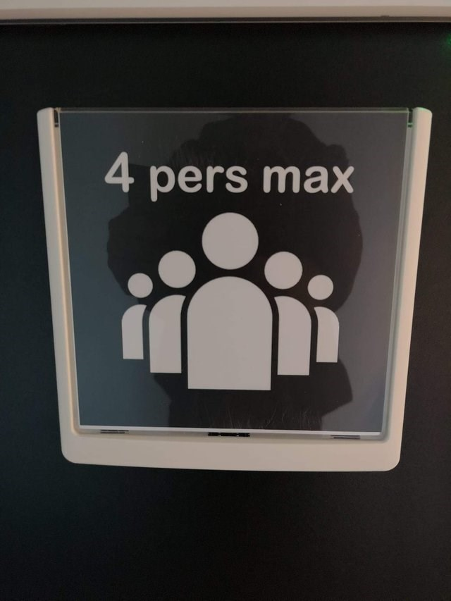 """""""four persons max"""" sign with drawing of five people"""