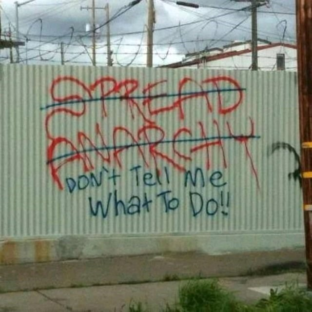 """graffiti encouraging to spread anarchy crossed out and replaced by graffiti saying """"don't tell me what to do"""""""