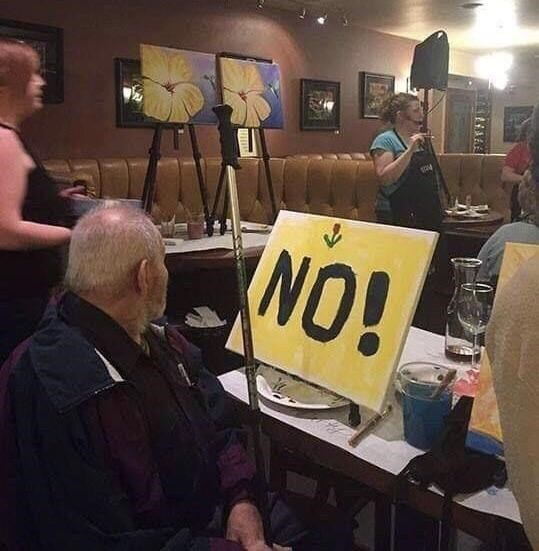 """man sitting in chair in front of large sign that says """"no!"""""""