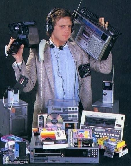 picture of man surrounded by different technological devices from the 80s and the 90s