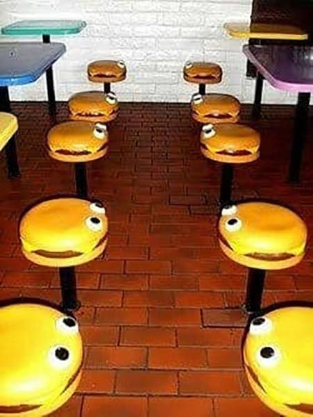 picture of a McDonald's in the 90s with seats shaped like burgers with eyes