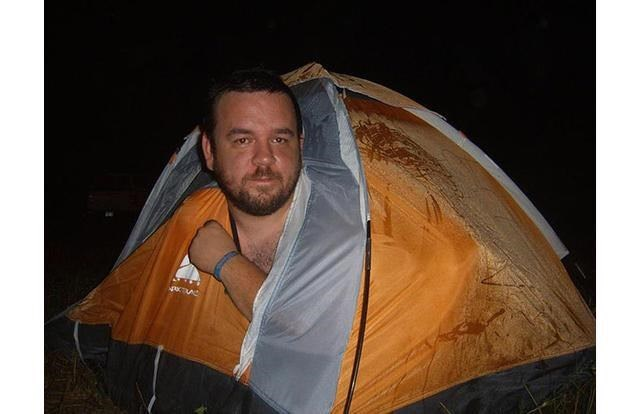 man in a tent that is too small for him