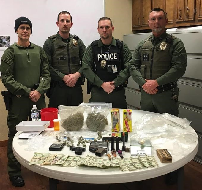 pic of a police department standing in front of a table full of things from a bust