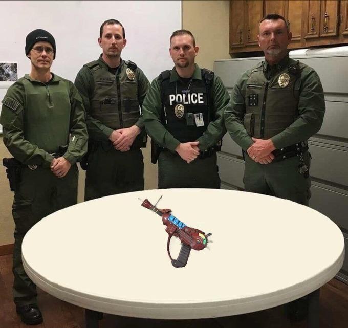 police department roast standing in front of a watergun